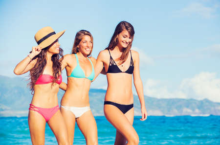 spring break: Group of Three Beautiful Attractive Young Women Walking on the Beach