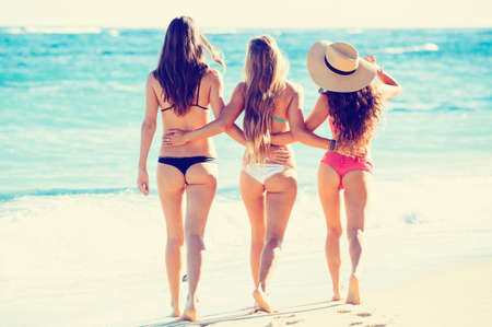 Group of Three Beautiful Hot Young Women on the Beach in Small Sexy Bikinis