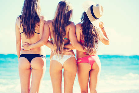 Group of Three Beautiful Hot Young Women on the Beach in Small Bikinis, Rear View of Sexy Butts photo