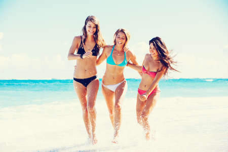 Group of Three Beautiful Attractive Young Women Walking on the Beach photo