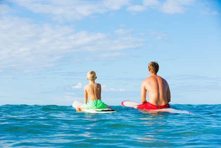 fatherhood: Happy Father and Young Son Going Surfing Together. Fatherhood Concept, Quality Time with Child.