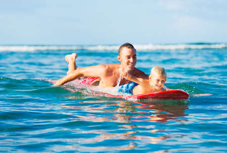 quality time: Happy Father and Young Son Going Surfing Together. Fatherhood Concept, Quality Time with Child.