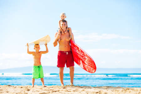 Father and Young Sons Going Surfing at the Beach Stock Photo