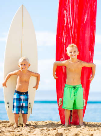 boardshorts: Young Boys With Surfboards on the Beach in Hawaii. Going Surfing. Stock Photo