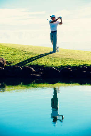 shot: Golfer Hitting Golf Shot with Club on Beautiful Golf Course on Vacation Stock Photo