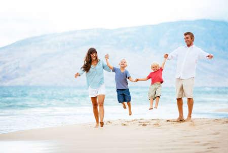 행복 한 젊은 가족 해질녘 해변을 걷고 스톡 콘텐츠
