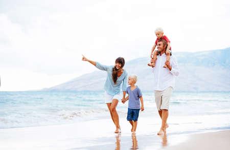 Gelukkig jong gezin wandelen langs het strand bij zonsondergang