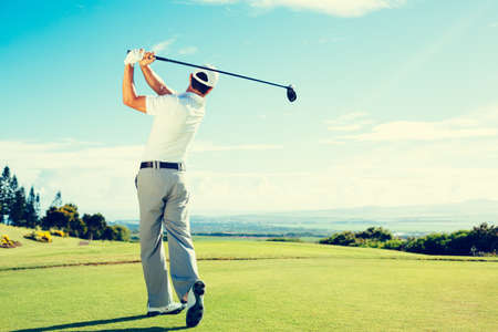action shot: Golfer Hitting Golf Shot with Club on Beautiful Golf Course on Vacation Stock Photo
