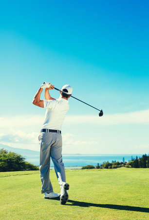 Golfer Hitting Golf Shot with Club on Beautiful Golf Course on Vacation Stock Photo