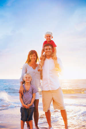 Happy Young Family on the Beach at Sunset photo