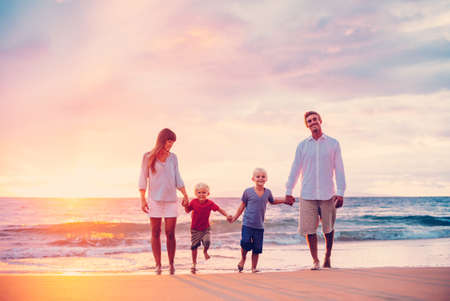Happy Young Family of Four on the Beach at Sunset Foto de archivo