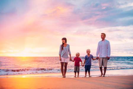 personas reunidas: Feliz familia de cuatro en la playa de la puesta del sol Foto de archivo
