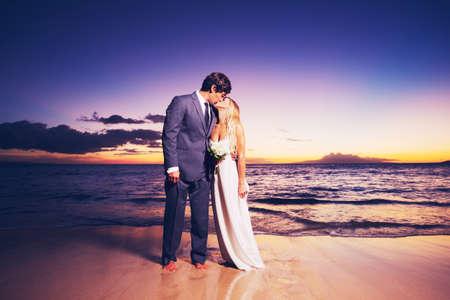 Gyönyörű esküvői pár, menyasszony és vőlegény csók a tengerparton naplementekor Stock fotó