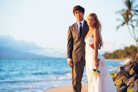 Beautiful Wedding Couple, Bride and Groom on the Beach at Sunset photo