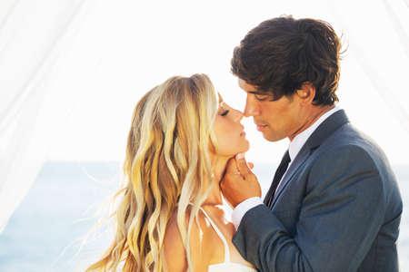 La boda, la novia y el novio romántico hermoso besándose y abrazándose en la puesta del sol
