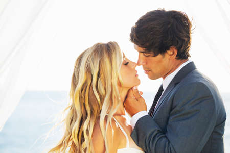 women kissing women: Wedding, Beautiful Romantic Bride and Groom Kissing and Embracing at Sunset Stock Photo