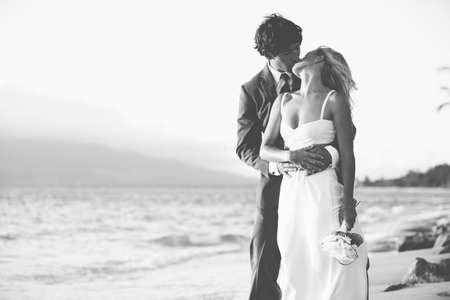 Mooie bruiloft paar, bruid en bruidegom kussen op het strand bij zonsondergang. Zwart-wit foto