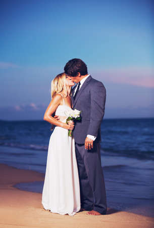 Beautiful Wedding Couple, Bride and Groom Kissing on the Beach at Sunset photo