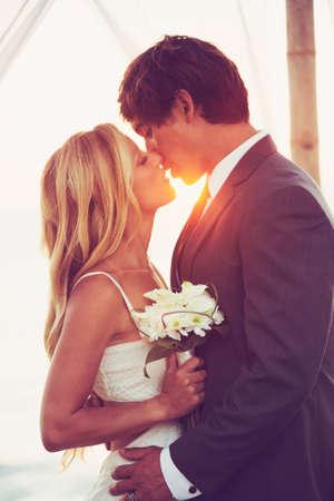 Mooie Zonsondergang Wedding by the Sea. Bruid en bruidegom kussen bij zonsondergang. Romantische Echtpaar.