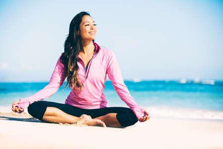 若い女性のビーチでのヨガの練習