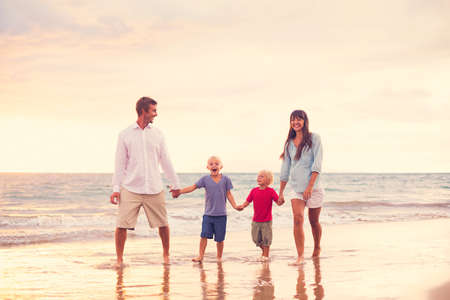 Happy Young Family Walking on the Beach at Sunset Reklamní fotografie