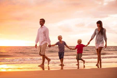 Gelukkig jong gezin van vier op het strand bij zonsondergang Stockfoto