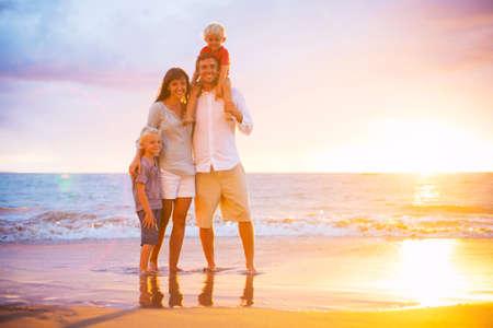 Portret van gelukkige jonge familie bij zonsondergang Stockfoto