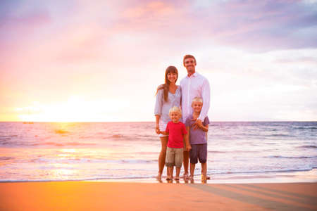Happy Young Family of Four on the Beach at Sunset 版權商用圖片 - 33847576