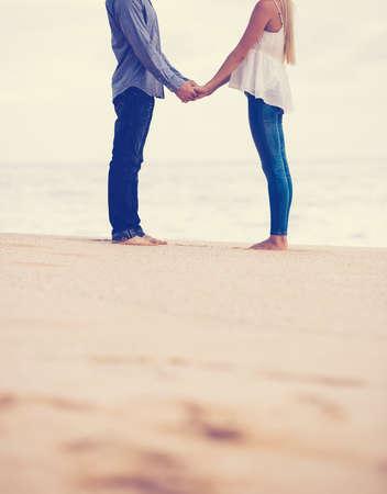 enamorados besandose: Pareja romántica en el amor de la mano en la playa al atardecer