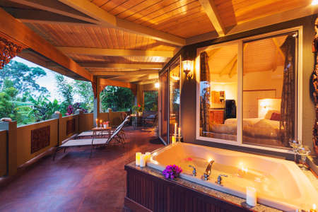 water hottub: Beautiful Romantic Deck on Tropical Home with Bathtub, Candles, and Flowers at Sunset