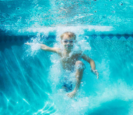 Underwater Young Boy Fun in the Swimming Pool with Goggles. Summer Vacation Fun. Banque d'images