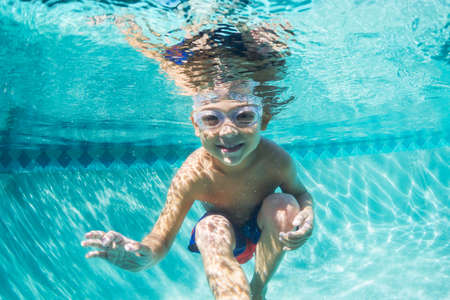 pool diving: Underwater Young Boy Fun in the Swimming Pool with Goggles. Summer Vacation Fun. Stock Photo