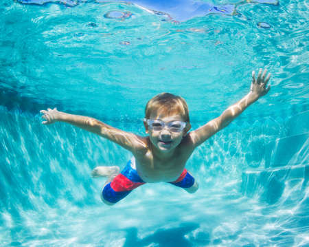 swimming: Underwater Young Boy Fun in the Swimming Pool with Goggles. Summer Vacation Fun. Stock Photo