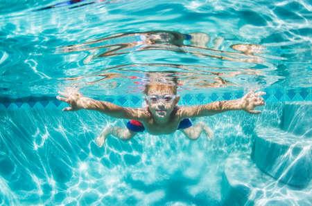 in action: Diversión bajo el agua Muchacho joven en la piscina con los anteojos. Vacaciones de verano de la diversión.
