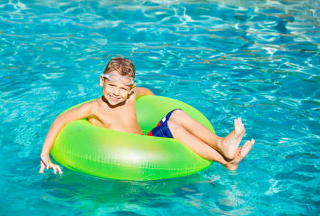 Young Kid Having Fun in the Swimming Pool On Inner Tube Raft. Summer Vacation Fun. Banco de Imagens