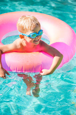 float tube: Little Kid Having Fun in Swimming Pool, with Goggles and Raft. Summer Vacation Fun.