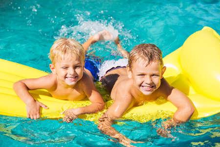어린 소녀 노란색 뗏목에 수영장에서 재미. 여름 휴가 재미.