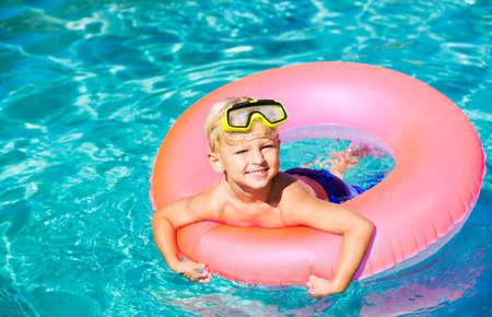 Young Kid Having Fun in the Swimming Pool On Inner Tube Raft. Summer Vacation Fun. Stock Photo