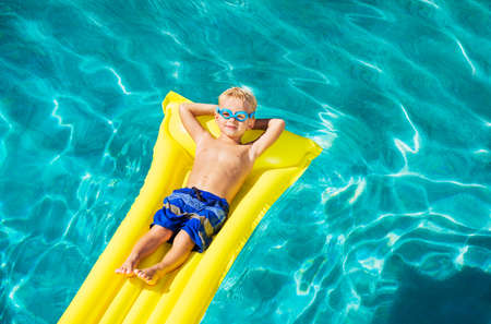 float tube: Young Boy Relaxing and Having Fun in Swimming Pool on Yellow Raft. Summer Vacation Fun. Relaxing Lifestyle Concept.