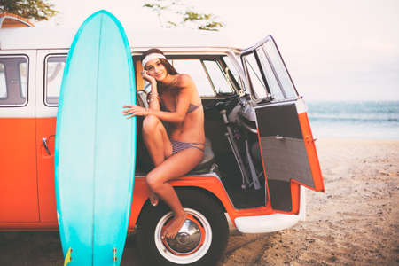 surfing: Beach Lifestyle, Beautiful Surfer Girl with Classic Vintage Surf Van on the Beach at Sunset