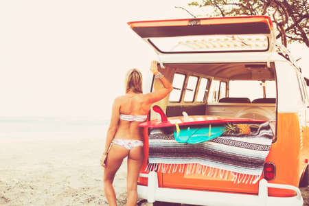surfing beach: Beach Lifestyle, Beautiful Surfer Girl on the Beach at Sunset with Classic Vintage Surf Van Stock Photo