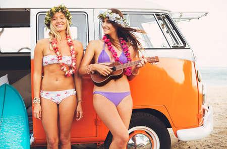leis: Belle Surfer Ragazze con Ukulele e Fiore Leis appendere fuori sulla spiaggia al tramonto con Classic Vintage Surf Van