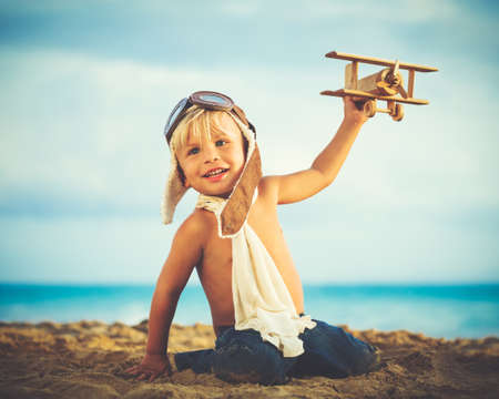 Small Boy Playing with Toy Airplane photo