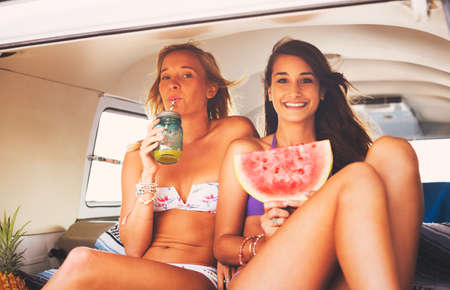 beach: Surfer Girls Beach Lifestyle, Friends Hanging out Eating Watermelon in the Back of Classic Vintage Surf Van on the Beach at Sunset