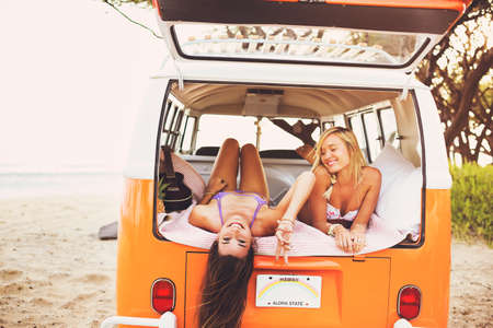 surfing: Surfer Girls Beach Lifestyle; Beautiful Surfer Girls Relaxing in the Back of Classic Vintage Surf Van on the Beach at Sunset