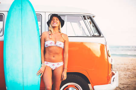surfing: Beach Lifestyle, Beautiful Surfer Girl on the Beach at Sunset with Classic Vintage Surf Van Stock Photo