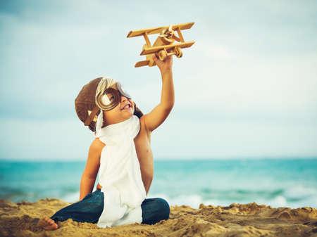 piloto de avion: Peque�o Muchacho que juega con el juguete del aeroplano Foto de archivo