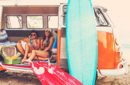 surfing waves: Beach Lifestyle. Beautiful Young Surfer Girls Having Fun Hanging Out in Vintage Surf Van. Best Friends.