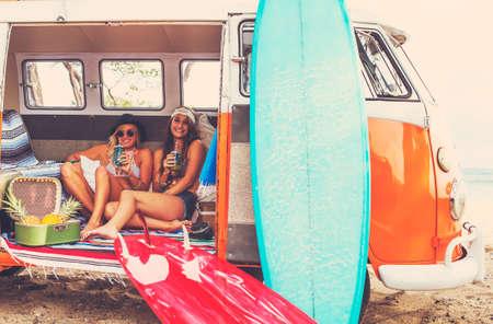 Beach Lifestyle. Beautiful Girls jovem surfista Tendo Fun pendurando para fora em Vintage Surf Van. Melhores Amigos.
