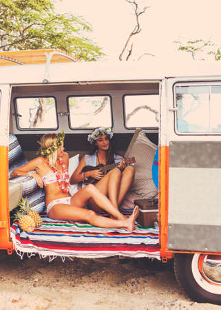 life style: Beach Lifestyle. Beautiful Young Surfer Girls Having Fun Hanging Out in Vintage Surf Van. Best Friends.
